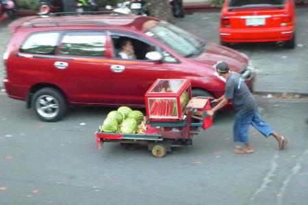 Vendeur ambulant poussant ses pastèques dans la rue au milieu des voitures / Street vendors pushing his load of watermelon