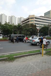 taxi en panne... 3 poussent la voiture, 2 regardent et un fait la circulation avec une branche de palmier... / broken down cab, three pushing, two watching and one stopping other cars with a palm tree.