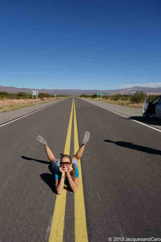 Caroline, lying down on la recta Tintin, a straight road at 3000m in Argentina